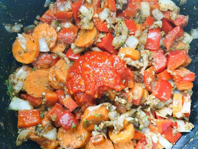 adding harissa to Moroccan stew